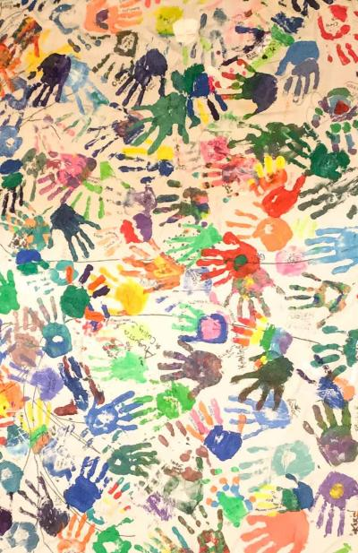 a canvas with multicolored handprints in all directions