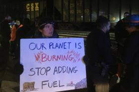 "Activists stand beside a coal train at night; one holds a sign reading ""Our planet is burning—stop adding fuel"""